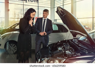 Car showroom employee man in a jacket shows the client a beautiful girl hood of the car. The buyer is delighted.