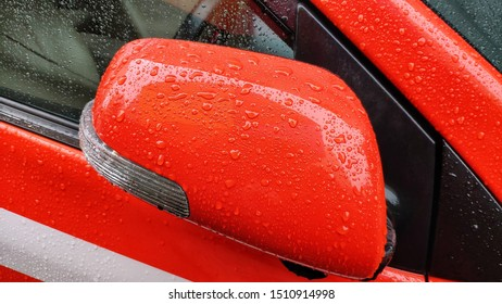 Car side mirror there is rainwater stuck. The atmosphere after the rain.