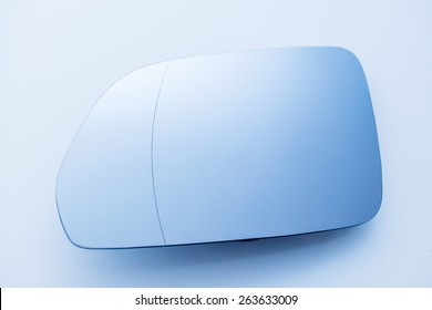 Car side rear view mirror on blue background - taken from above with no reflection as tilt-shift lens was used