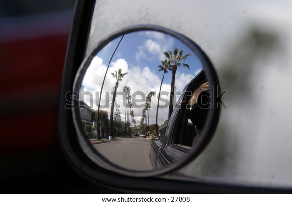 a car side view mirror shows a reflection of palm trees lined up along a city street with white fluffy clouds