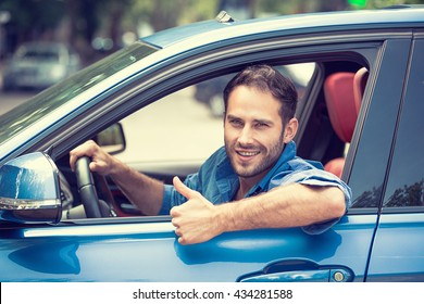 Car side window. Man driver happy smiling showing thumbs up driving sport blue car isolated outside parking lot background. Handsome young man excited about his new vehicle. Positive face expression
