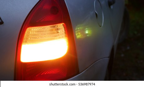 car silver blinker is blinking in the evening standing still