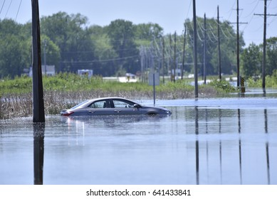 A car sits stranded after getting stuck on a flooded road