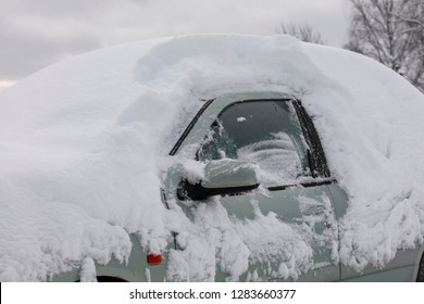 A car with a lot of snow on top in Finland. The windshield is completely covered.