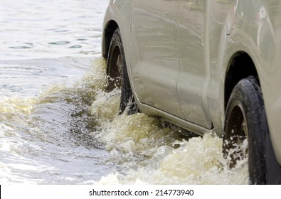 Car splashes through a large puddle on a flooded street