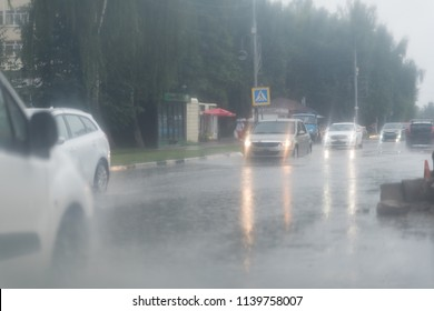 Car splashes trough water on a partly flooded road.