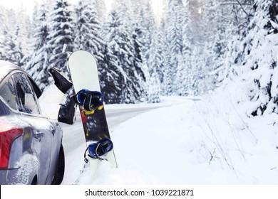Car standing in a beautiful snowy place in winter, from the window car women,s  legs in snowboard