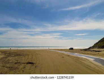 A car standing on the beach and people walking along the sea in Baylys Beach, New Zealand