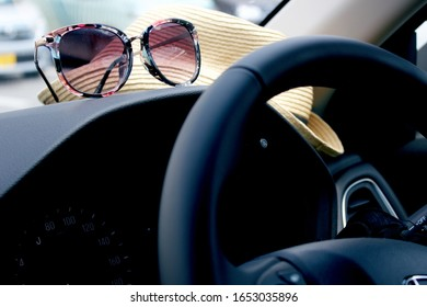 Car steering wheel, sunglasses and straw hat on dashboard