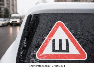 Car sticker on the rear snow-covered glass of the car warning drivers that the car is fitted with wheels with studded rubber