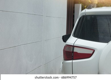 Car stop on parking area beside wall.