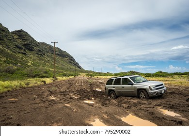 Car stuck in muddy road. Mud road leading along north coast of Oahu, Hawaii.