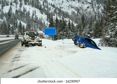 Car stuck in a snow bank on the side of the highway
