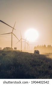 car at sunset in a wind farm with wind turbines, with the sun in the golden hour