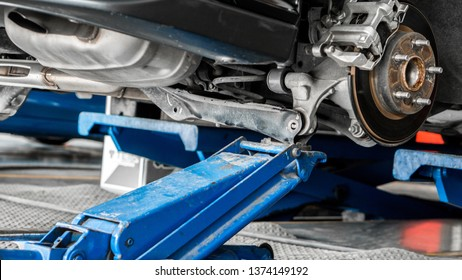 Car suspension and mechanic service concept - Car suspension service with HYDRAULIC FLOOR JACK in maintenance car garage and copy space, use for car suspension service content