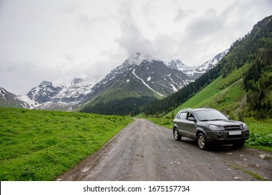 car SUV stands on the road against the background of snow year, landscape spring in the mountains