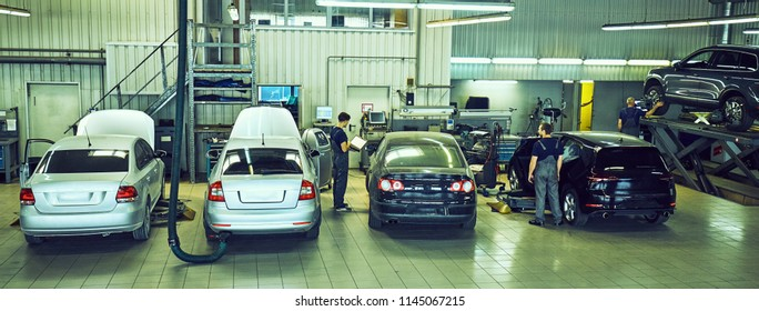 Car technician repairing car in workshop service station