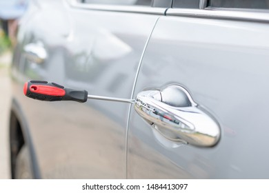 Car technician wearing white gloves and using screwdriver to fix, repair or open the door of modern car