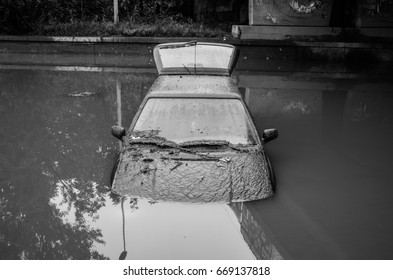 A car that was destroyed in a storm, the flooded vehicle is a result of a hurricane.