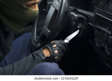 Car theft in mask and black gloves breaking down the car lock. Carjacking concept