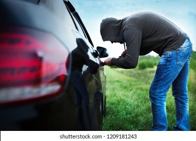 car thief in action, a man in a hood breaks a screwdriver car door