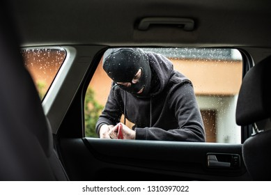 Car thief in a balaclava is trying to break into a car using a crowbar