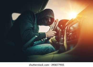 Car Thief in a Black Mask and Black Glasses. Car Thief Inside the Modern Car.