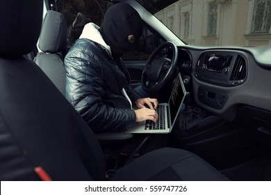 Car thief hacking security systems with laptop computer