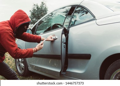 Car thief in hoodie managed to unlock the car using the smartphone and car link application. Man with masked face got the access to the vehicle cabin by mobile app. Criminal unlocks the automobile