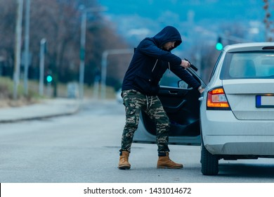 The car thief is pulling the car owner out of his car and trying to get the car while pointing a loaded gun at the drivers head.