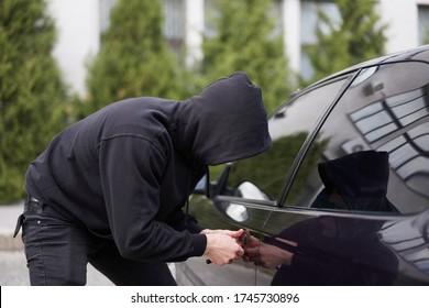 Car thief steal car breaking door criminal job burglar Hijacks  Auto thief black balaclava hoodie trying  break into vehicle screwdriver  Street crime violence gangster robber automobile parking