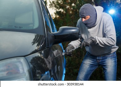 Car thief stealing a car. Trying to pick the lock.