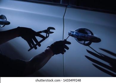 Car thief using a tool to break into a car