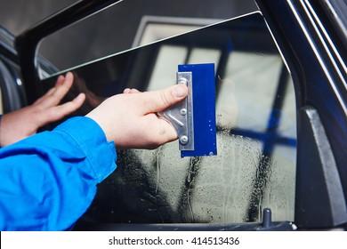Autotinte. Automobil-Mechaniker, der Folienfolie verwendet