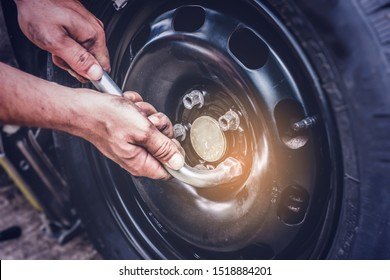 car tire change, hands on wrench closing screws after changing flat tire