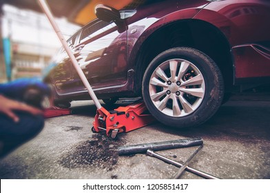 Car tire changed for maintenance in garage using hydraulic jack - car maintenance concept