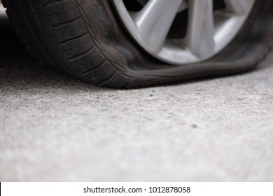 Car tire leak because of nail pounding. flat tyre on road. Flatten punctured auto wheel