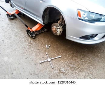 The car is at the tire shop. Under the jack the car in car-care center. The car with the removed wheel