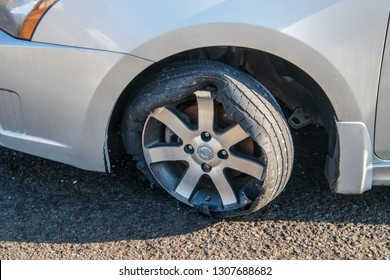 Car tire that has a blowout with rim and car damage. Tire is coming off of rim. Tire is on a car that is on an asphalt street