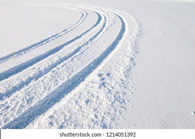 Car tire tracks in fresh snow.