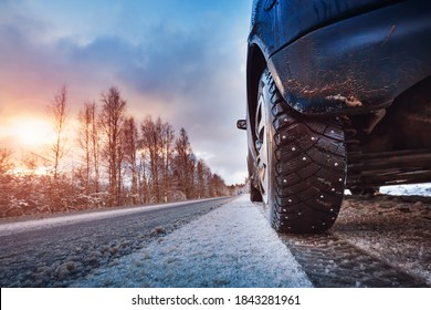 Car tires on winter road covered with snow. Vehicle on snowy way in the morning