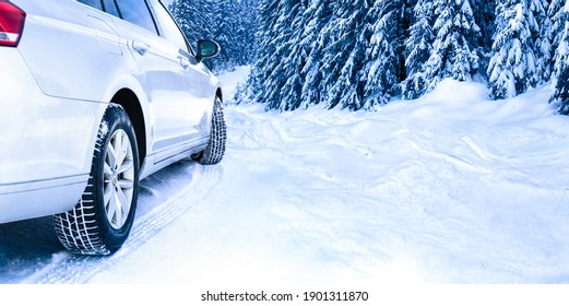 Car tires on winter road covered with snow. Tires on snowy highway detail. Family trip to ski resort concept.