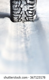 Car tires on winter road, shallow depth of view