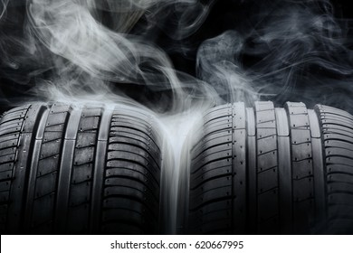 Car tires and smoke on black background