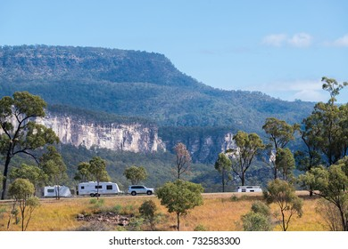 Car towing a caravan with mountains in the background