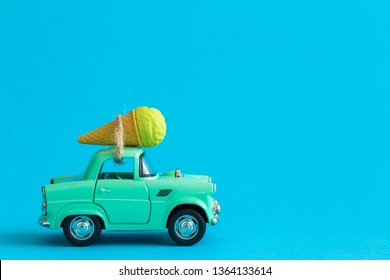 Car toy and ice cream against blue background on the road abstract.
