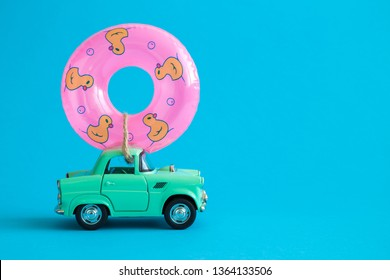 Car toy and inflatable pool float against blue background on the road abstract.