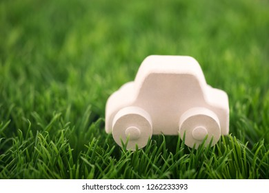 Car toy on green grass. Eco driving concept