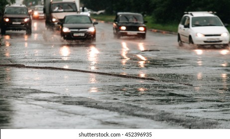 Car traffic in bokeh when heavy rain drops in concrete