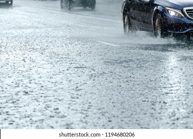 car traffic driving on flooded city road during rain. water splashing from car wheels